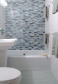 Glass mosaic feature wall, reglazed original tub and penny tile floor